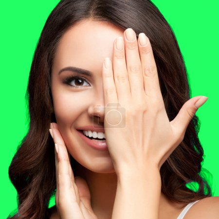 Woman with one eye closed by hand, on green chroma key backgroun