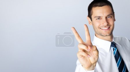 Smiling businessman showing two fingers, over grey