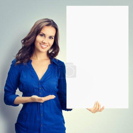fröhliche brünette Frau zeigt leeres Schild