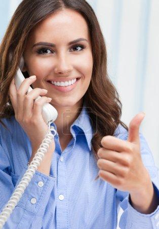 Photo pour Portrait d'heureux sourire belle jeune femme d'affaires ou de soutien à la clientèle travailleuse du téléphone montrant pouce vers le haut signe de la main geture, au bureau. Concept de service d'assistance client . - image libre de droit