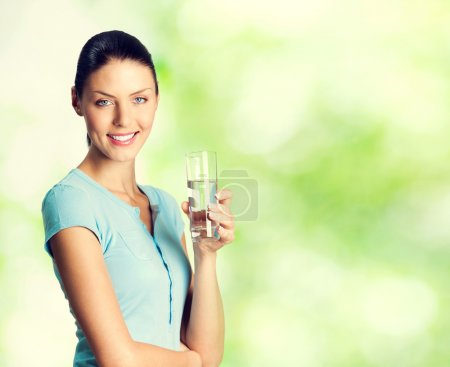 Photo for Young happy smiling lovely woman with glass of water, outdoor, with blank copyspace area for text or slogan - Royalty Free Image