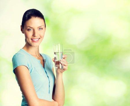 Lächeln schöne Frau mit einem Glas Wasser, im Freien