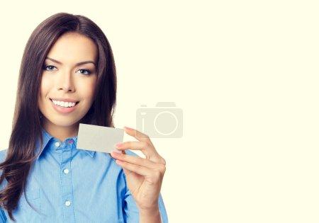 Photo pour Portrait de femme d'affaires souriant gai montrant des affaires ou carte de crédit en plastique avec fond blanc pour un message texte ou un slogan - image libre de droit