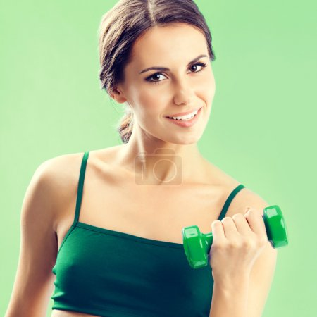 Photo pour Portrait de sourire jeune belle femme en tenue de fitness exercice avec haltère, sur fond vert - image libre de droit
