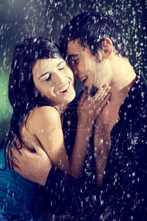 Young couple hugging and under a rain, in passion
