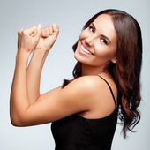 Smiling young woman happy gesturing, over bright grey
