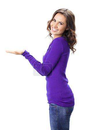 Photo pour Joyeux sourire belle jeune femme montrant copyspace ou quelque chose, en violet vêtements décontractés, isolé sur fond blanc - image libre de droit