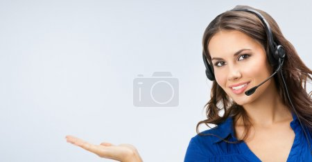 Photo for Portrait of happy smiling beautiful young support phone operator showing blank copyspace area for slogan or text, posing at studio - Royalty Free Image