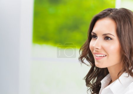 Young smiling cheerful businesswoman at office, with copyspace