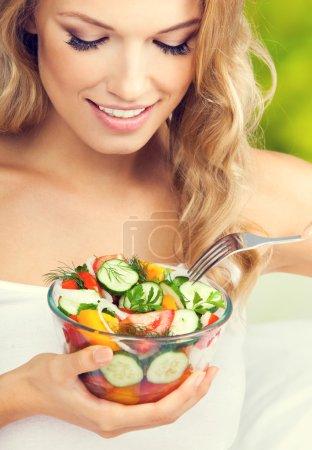 Woman eating salad, indoors