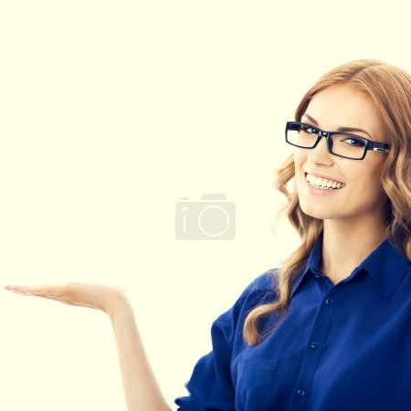 Photo for Portrait of smiling beautiful young businesswoman in blue clothing showing something or blank copyspace area for slogan or text message - Royalty Free Image