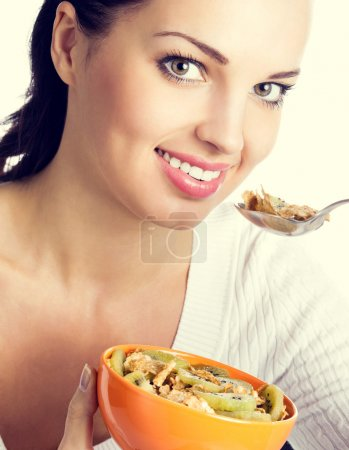 Photo for Portrait of young smiling woman eating muesli or cornflakes and kiwi - Royalty Free Image