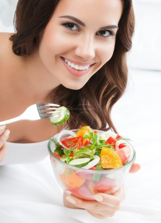 smiling young woman eating salad, on bed