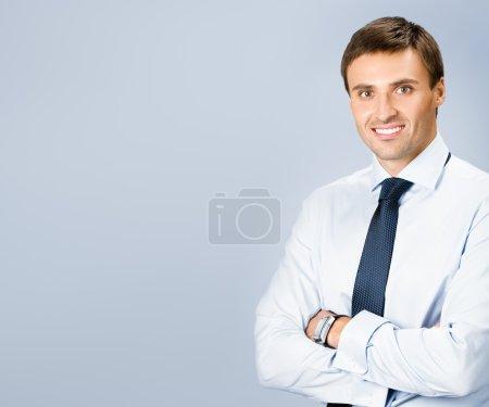 Foto de Retrato de hombre joven sonriente feliz, con copyspace, sobre fondo gris - Imagen libre de derechos