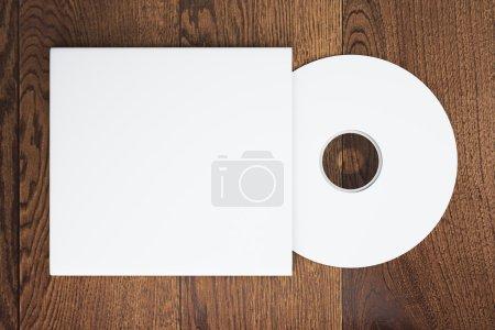 Photo pour Vue de dessus du disque compact blanc vierge avec couvercle sur une table en bois. Maquette, rendu 3D - image libre de droit