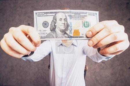 Photo pour Homme tenant un billet de cent dollars sur fond de béton - image libre de droit