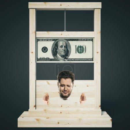 Photo pour Concept de dette avec l'homme sur le point de se faire couper la tête sur une guillotine en bois clair, isolé sur fond sombre. Rendu 3D - image libre de droit