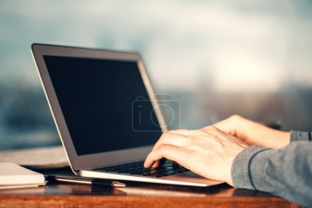 Man with grey sleeves typing on laptop keyboard