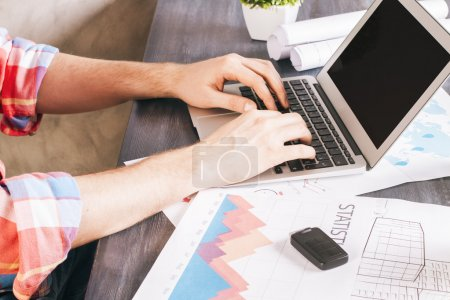 Photo for Wooden designer tabletop with various items and man hands typing on laptop keyboard - Royalty Free Image