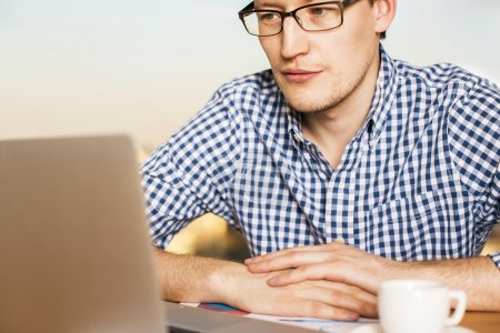 Photo for Young caucasian male sitting at desk with coffee and laptop, looking at the screen - Royalty Free Image
