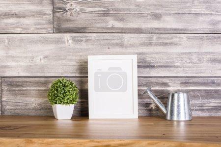 Photo pour Cadre vierge, plante et arrosoir sur fond bois. Maquette - image libre de droit
