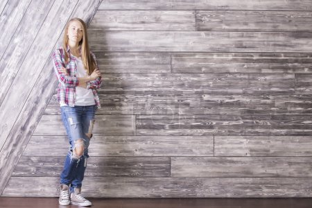 Thinking girl against wooden wall