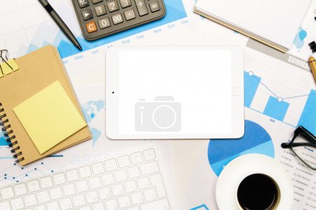 Photo for Topview of tabletop with blank white tablet, keyboard, spiral notepad and other office tools on business charts. Mock up - Royalty Free Image