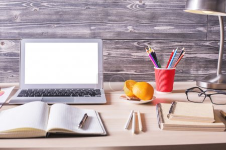 Photo for Closeup of office desktop with blank white laptop, notepad, orange slices, glasses, lamp and other items on wooden background. Mock up - Royalty Free Image