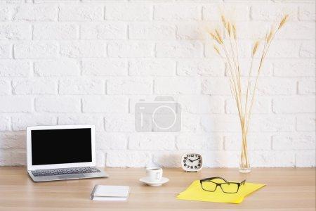 Photo pour Lieu de travail lumineux avec ordinateur portable vierge, bloc-notes, tasse à café, horloge, verres sur feuille de papier jaune et épis de blé sur fond de mur de briques. Maquette - image libre de droit