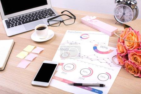 Foto de Escritorio diseño creativo con informe de negocio, la pantalla del teléfono inteligente en blanco, flores, laptop, taza de café, reloj despertador y otros artículos. Mock up - Imagen libre de derechos