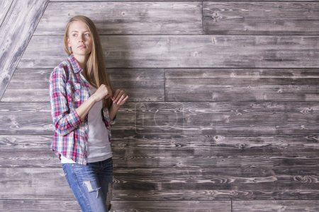 Girl against wooden wall