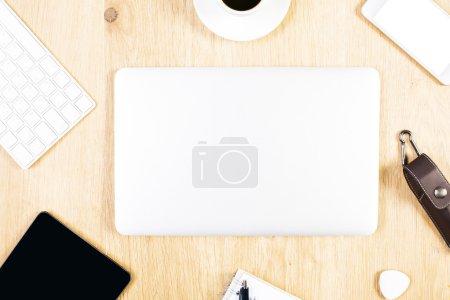 Foto de Portátil cerrada en madera escritorio con dispositivos electrónicos y artículos de papelería. Mock up - Imagen libre de derechos