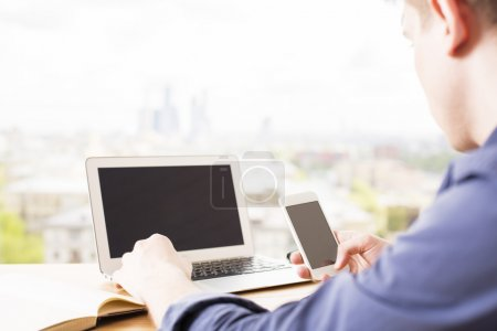 Man using laptop and phone