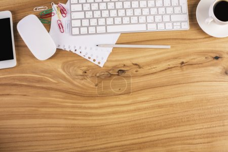 Photo for Top view of wooden office desktop with smartphone, computer mouse and keyboard, coffee cup and stationery items. Mock up - Royalty Free Image
