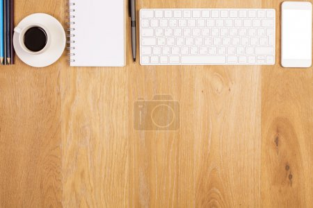 Photo for Top view of wooden desktop with coffee cup, spiral notepad, blank white smartphone, keyboard and other items. Mock up - Royalty Free Image