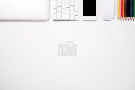 Photo pour Vue du dessus de bureau blanc avec ordinateur portable fermé, keybopard, téléphone vide, souris d'ordinateur et crayons colorés. Maquette - image libre de droit
