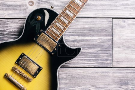 Closeup of black and yellow electric guitar on wooden background