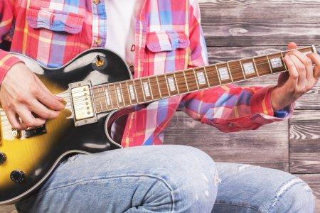 Guy playing guitar closeup