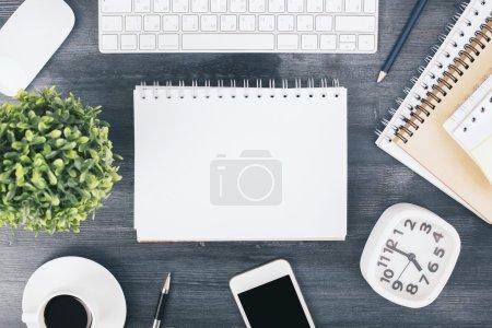 Photo pour Vue du dessus du bureau en bois sombre avec bloc-notes en spirale vierge, smartphone, plante, horloge, clavier et autres éléments. Maquette - image libre de droit