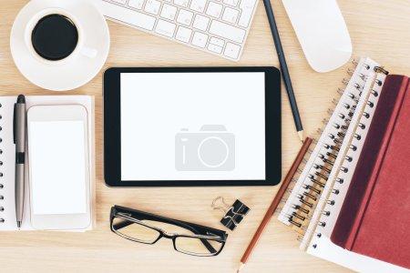 Photo pour Vue de dessus de bureau en bois avec coussin blanc vierge, téléphone mobile, verres, tasse à café, bloc-notes et autres articles. Maquette - image libre de droit
