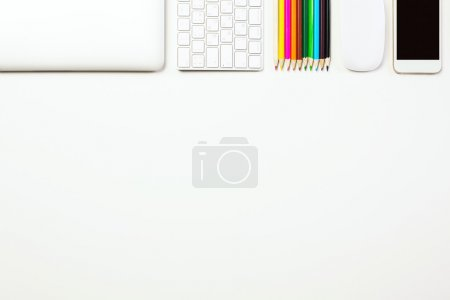 Photo for Top view of white office desktop with closed laptop, computer keyboard, colorful pencils, mouse and smart phone. Mock up - Royalty Free Image