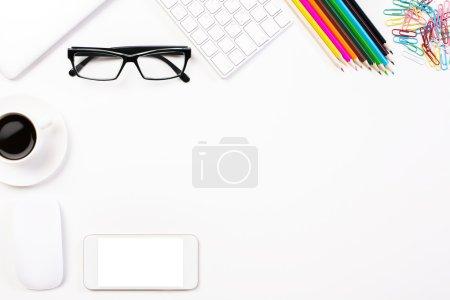 Photo pour Vue du dessus de bureau blanc avec téléphone vierge, tasse à café, lunettes, crayons de couleur, clavier et autres articles. Maquette - image libre de droit