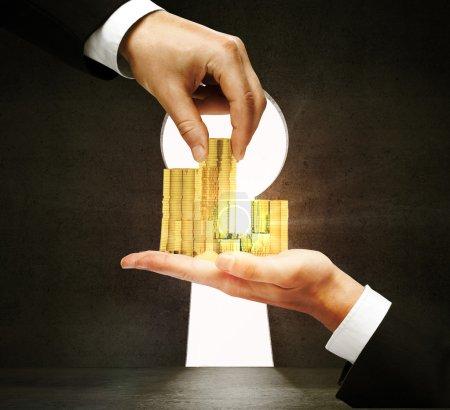 Hand taking golden coins