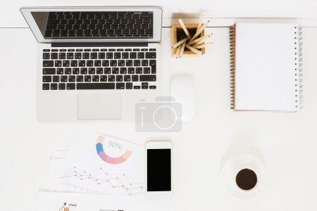 Photo pour Vue du dessus du bureau léger avec smartphone vierge, rapport d'entreprise, tasse à café, bloc-notes en spirale, autres articles de papeterie et ordinateur portable. Maquette - image libre de droit