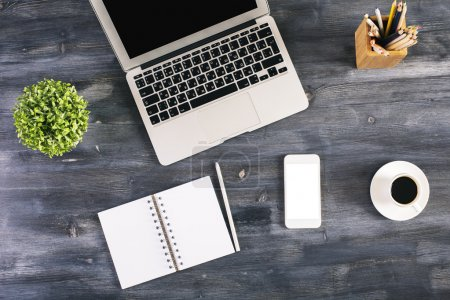 Photo for Top view of blank spiral notepad, white smartphone, coffee cup, laptop, plant and other items on dark wooden office desktop. Mock up - Royalty Free Image