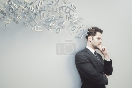 Thinking businessman with hand at chin on light grey background