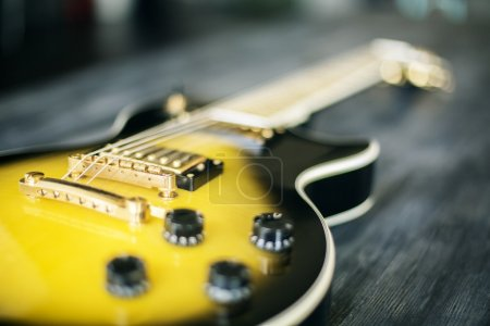 Photo for Closeup of black and yellow electric guitar on blurry dark wooden desktop - Royalty Free Image