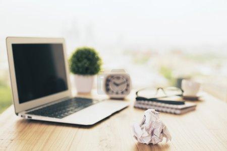 Foto de Pedazo de papel arrugado en escritorio de oficina de madera con computadora portátil borrosa, planta, reloj, vasos, café y artículos de papelería. Prepárate. - Imagen libre de derechos