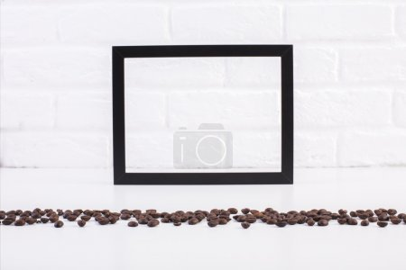 Photo for Front view of bright table with coffee beans and blank see-through picture frame on white brick wall background. Mock up - Royalty Free Image