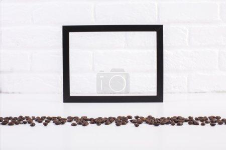 Foto de Vista frontal de la mesa brillante con granos de café y marco de imagen a see-through en blanco sobre fondo de pared de ladrillo blanco. Mock up - Imagen libre de derechos